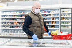 Adult man in the refridgerated goods area at a supermarket choosing products with gloves and a mask on. Conscientious shopping during the virus outbreak.
