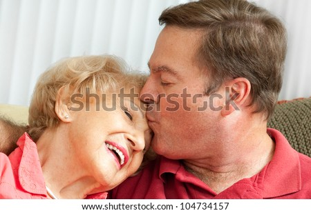Adult man kissing his elderly mother on the forehead.  Closeup portrait.