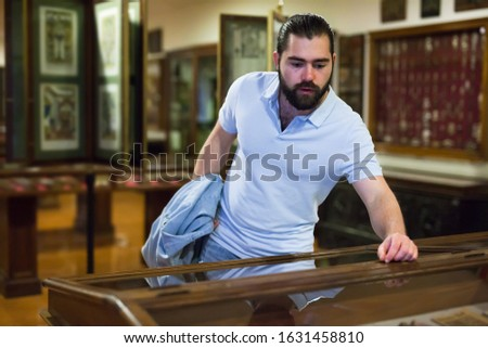 Adult man looking at exhibits in glazed stands in historical museum