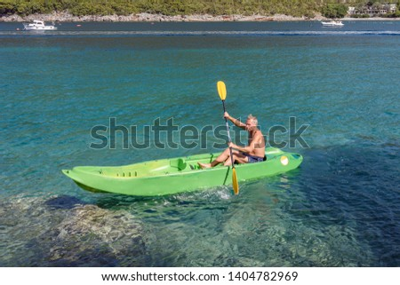 Adult man, pensioner is floating on a boat. Activity leisure and travel on the turquoise waters of Adriatic Sea. Healthy elder enjoying summer day outdoors. Active retirement concept #1404782969