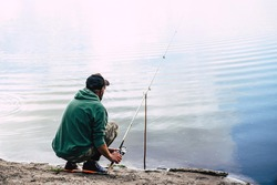 adult man, professional fishing on a lake in cloudy weather, outdoor recreation, fresh air, male hobby