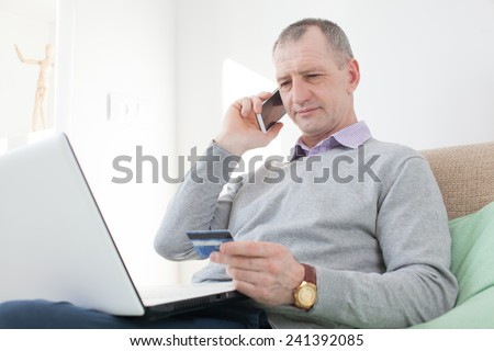Adult man reading a credit card number during phone call