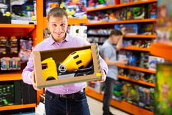Adult man shopping in store of kids toys, looking for big toy car