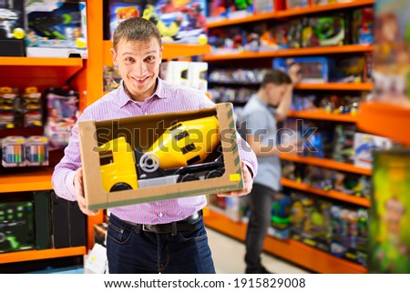 Adult man shopping in store of kids toys, looking for big toy car ストックフォト ©