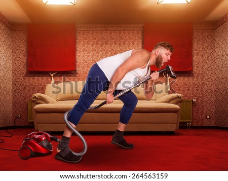 Adult man sings to the vacuum cleaner at home interior Stock fotó ©