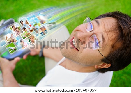 Adult man sitting on grass in park and using social media to look through new photo of his friends