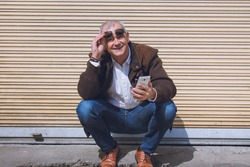 adult man squatting using mobile phone in the city