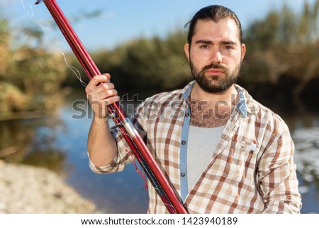 Adult man standing outdoors with angling rod planning to fishing