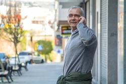 adult man talking with mobile phone in the street