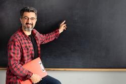 Adult man teacher showing empty blackboard.