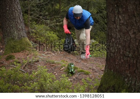Adult man volunteer in red gloves removes plastic trash in forest, caring for environment. #1398128051