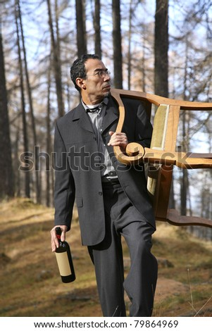 adult man walking in the woods with the chair on the shoulders