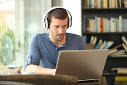 Adult man wearing headphones using a laptop e-learning in a coffee shop or home