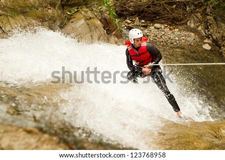 adult man wearing waterproof equipment descending a waterfall