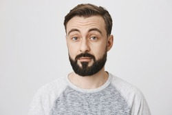 Adult man with a beard and moustache looking surprised over a white background. Person just found out that sister is going out with his best friend. He did not expect that coming.