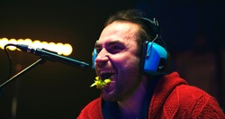 Adult man with headset chewing fresh vegetables and laughing near microphone while recording soundtrack for film