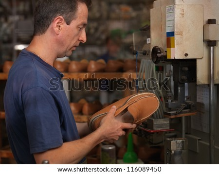 adult man working in a shoe factory, checking the quality of the products - stock photo