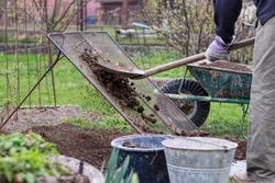 Adult man works on garden. Man shovel soil through homemade screen for sorting on stones and clay. Homemade device for sifting clay. Shovel, wheel. Landscaping work. Hard working man. Manual work.