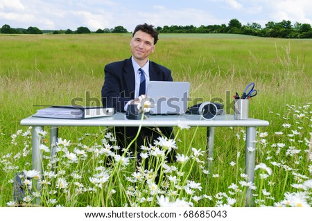Adult Manager works in a suit at a desk in the open in the middle of a field of flowers and smiling at the camera
