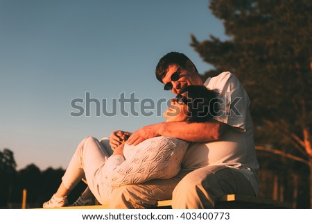 Adult married couple on a bench. Husband embraces his wife.