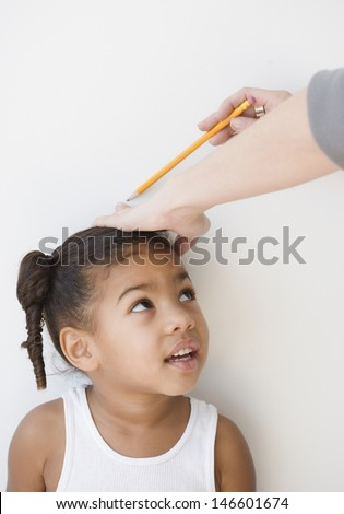 Adult measuring little girl's height