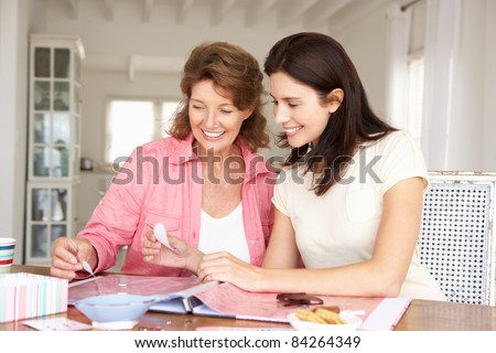 Adult mother and daughter scrapbooking