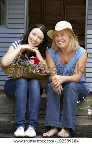 Adult mother and daughter sitting on veranda
