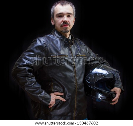 Adult motorcyclist in brown leather jacket. Studio waist portrait on dark background.