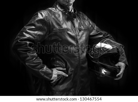 Adult motorcyclist in leather jacket. Studio waist portrait on dark background.