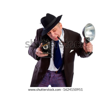 adult news photographer in a costume of the last century fashion and a wide-brimmed hat with an old camera and flash diligently takes a photo