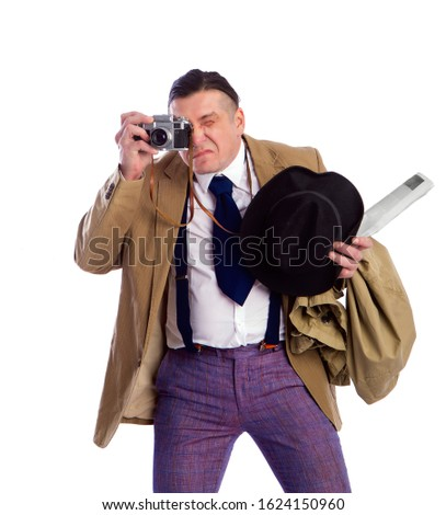 adult news photographer in a costume of the last century fashion and a wide-brimmed hat with an old camera diligently takes a photo