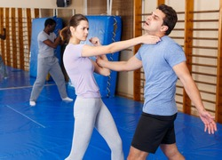 Adult people practicing effective techniques of self-defence in training room