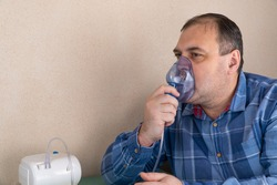 adult person makes inhalations with the help of nebulizer. patient breathes through an Oxygen Mask. man is being treated for respiratory diseases. prevention of asthma