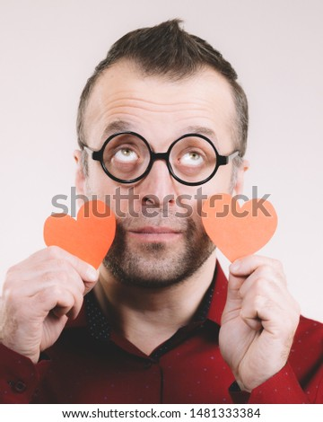 Adult positive man holding red hearts. Male in love. Romance feelings valentines day concept