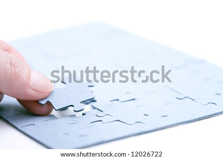 stock photo : Adult's hand holding jigsaw puzzle over the hole in jigsaw ...