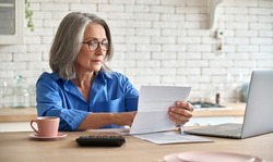 Adult senior 60s woman working at home at laptop. Serious middle aged woman at table holding document calculating bank loan payments, taxes, fees, retirement finances online with computer technologies