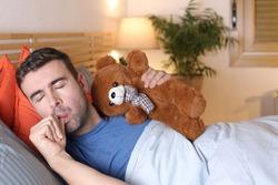 Adult sleeping with teddy bear