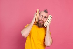 Adult smiling casual clothes guy with beard hugs favorite books to himself isolated on pink background