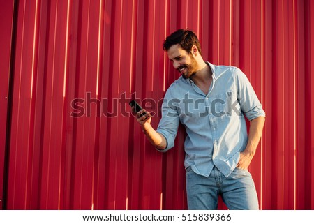 adult smiling man in  jeans outfit standing on red wall with a cellphone in hands #515839366