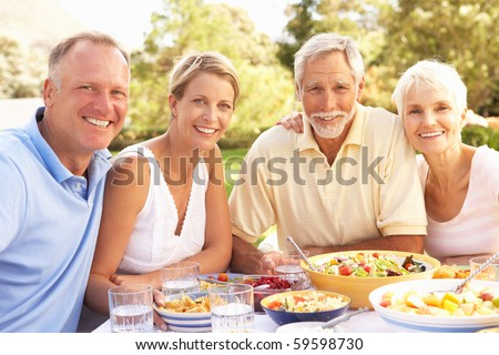 Adult Son And Daughter Enjoying Meal In Garden With Senior Parents - stock photo