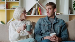 Adult son visit older mother, enjoy pleasant warm friendly talk at informal atmosphere drinking tea seated on couch