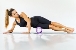 Adult sporty woman doing fascia exercise on the floor - Caucasian female using foam massage roller - tool for leg thigh tension and muscle pain release - physical therapy and training concept