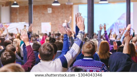 Adult students listen to professor's lecture in class room, hands up for queue of asking question to Lecturer or poll voting.  Rear view, Audience Watching a Presentation. Business, education.