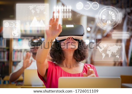 Adult students using VR simulators for virtual statistics for studying. Man and woman in virtual reality glasses sitting at desks with laptops and touching air. VR simulation concept