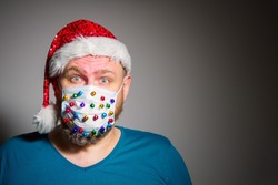 Adult surprised man in Christmas decorated mask celebrate xmas holidays at home because coronavirus. New normal, social distancing