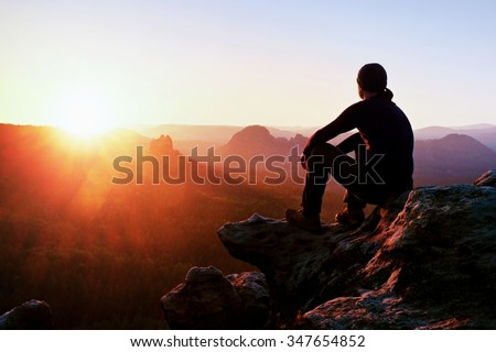 Adult tourist in black trousers, jacket and dark cap sit on cliff\'s edge and looking to misty hilly valley bellow