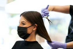 Adult woman at hairdresser wearing protective mask due to coronavirus pandemic