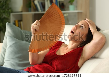Adult woman fanning suffering heat stroke sitting in the livingroom at home