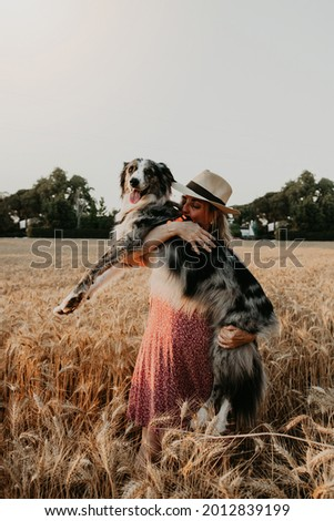 Adult woman hugging her adorable border collie dog in a wheat fiel on summer. Love for animals concept.  Foto stock ©