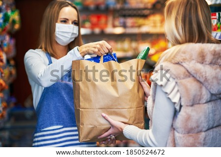 Adult woman in medical mask picking up order in grocery store Stock photo ©